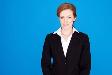 auburn: Smart efficient redhead businesswoman standing smiling in a stylish black jacket