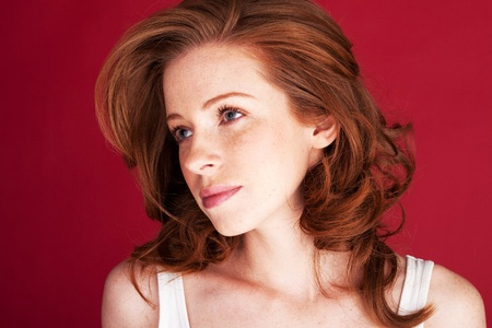 wistful: Beautiful redhead woman looking sieways with large wistful eyes.