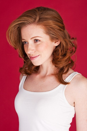 Beautiful young redhead woman in a sleeveless summer top looking to left of frame. Stock Photo