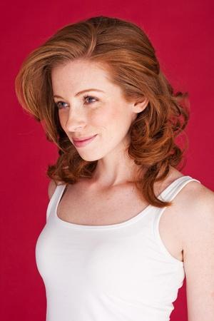 Piękna młoda kobieta rude w bez rękawów szczycie letnim patrząc na lewo od klatki.