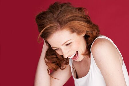 Attractive redhead woman having a good laugh and showing a lovely sense of humour Stock Photo - 12587950
