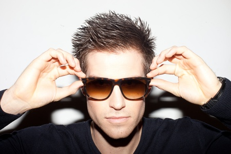 spiky: Trendy young man with spiky hair with his hands raised to a pair of sunglasses.