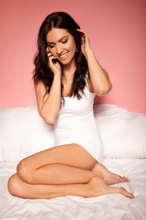 Beautiful brunette woman relaxing curled up on her bed talking on her mobile phone. photo