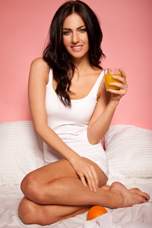 Beautiful woman curled up on her bed holding her early morning glass of fresh orange juice and with a whole orange nestling in the bedclothes nearby