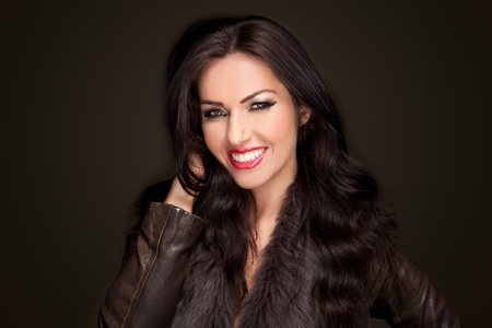dark haired: Dark haired smiling beautiful woman in a fashionable jacket against a dark background