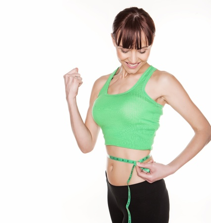 Happy smiling woman with a lovely figure measuring her tiny waist with a tape measure