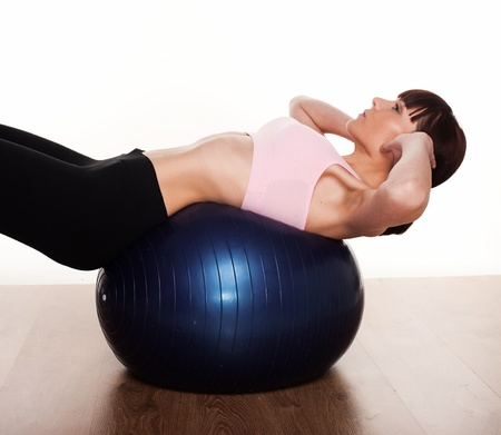 Woman leaning backwards over a pilates ball exercinig her stomach and back muscles photo