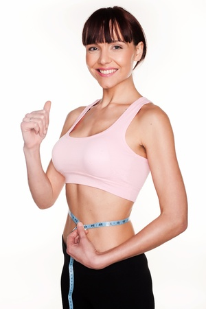 Smiling young woman giving a thumbs up sign while measuring her waist to show she is happy with her weightloss photo