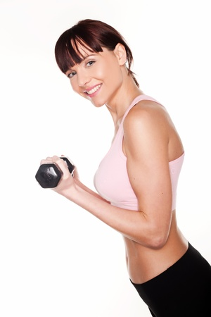 Sideways view of an athletic young woman holding a dumbbell in her hand photo