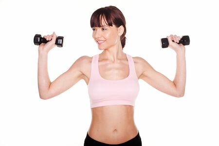 Athletic woman holding two dumbbells in her hands above her shoulders during a workout photo