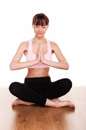 Attractive young woman with serene expression and eyes closed meditating in the lotus postion during yoga practise Stock Photo - 12586296