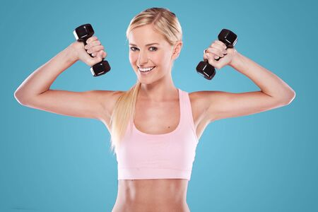 hand bra: beautiful happy blonde fitness model  on blue background Stock Photo