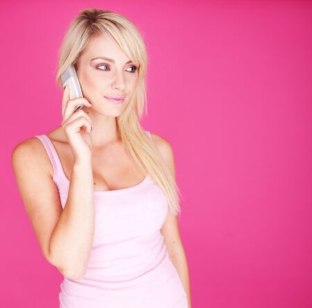 Portrait of young blonde woman over the phone on pink background copyspace photo