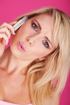 close-up Portrait of young blonde woman talking on cellphone with  expression  photo