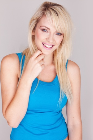 woman on top: Close up portrait  of a attractive young blond woman wearing a blue top. Stock Photo