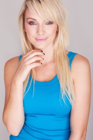 Close up portrait  of a attractive young blond woman wearing a blue top. Stock Photo - 12589644