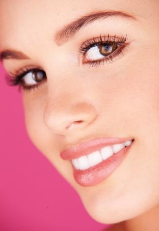 dientes sanos: Retrato de mujer con unos dientes sanos blancos sobre fondo de color rosa