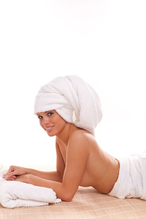 Young woman wrapped towel isolated on white background photo