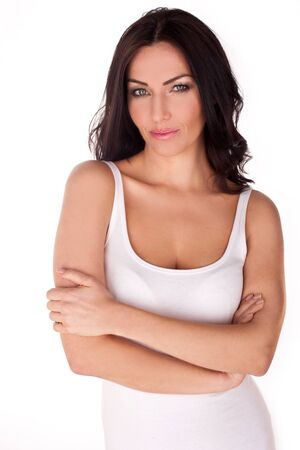 tank top: Brunette woman on a white background wearing a white tank top with arms crossed in front of her