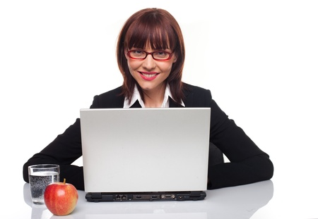 coporate: Healthy businesswoman seated at her desk in front of her laptop with a glass of fresh clean water and an apple