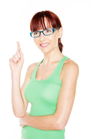 woman pointing up: Pretty young redhead woman in glasses and a green summer top pointing up above her head with her index finger isolated on white