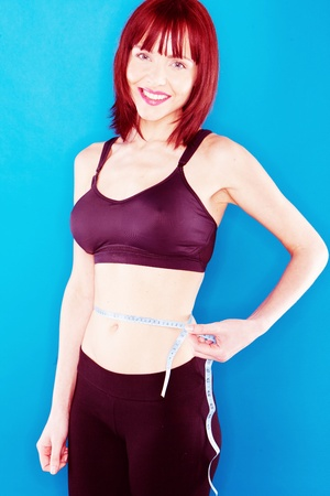 yoga pants: smiling woman in a sports outfit of black tank top and black black yoga pants, her left hand holding a tape measure around her waist, on blue background Stock Photo