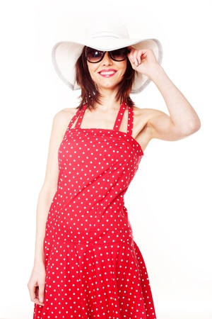 brim: Pretty young model wearing a floppy wide brim hat with a red polka dot dress and sunglasses isolated on white