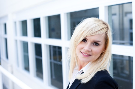 rule of thirds: Attractive young blonde woman standing in front of a white framed window facade which gives the image strong architectural perspective Stock Photo