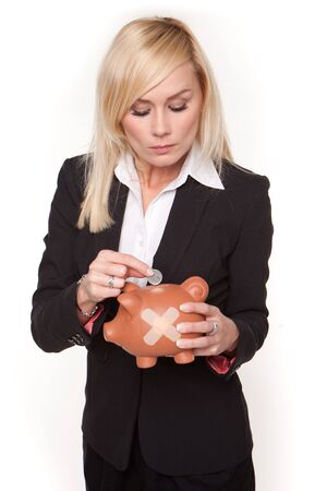 contemplates: Woman contemplates the unhealthy state of her finances as she places a single coin into a piggy bank with a plaster on its side Stock Photo