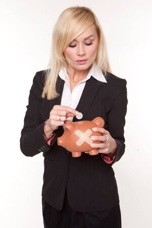 sticking: Woman contemplates the unhealthy state of her finances as she places a single coin into a piggy bank with a plaster on its side Stock Photo