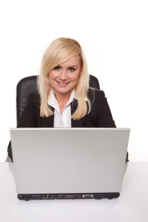 personal assistant: Smiling friendly secretary or personal assistant sitting working at her laptop isolated on white Stock Photo