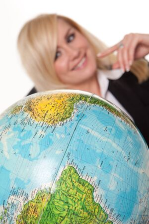 wanting: Beautiful young blonde woman sitting studying a world globe and planning her dream holiday