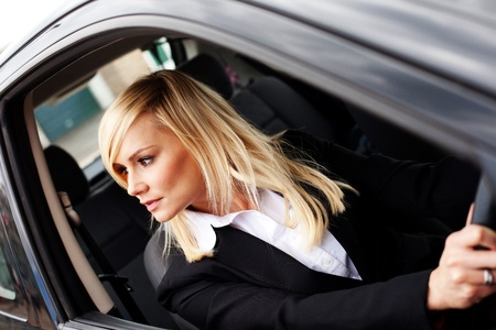 reversing: View through the drivers window of an attractive woman looking over her shoulder and reversing a car