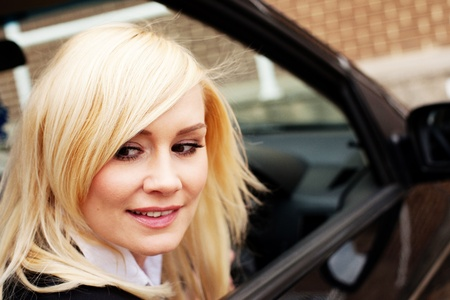reversing: Attractive blonde woman driver looking out of her window while reversing her car