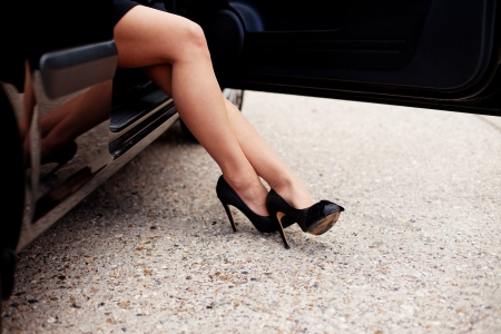 Cropped image of sexy stockinged female legs in fashionable high heeled shoes alighting from a car photo