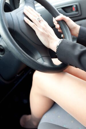 Cropped view image inside a motorcar of a woman driver with her hand on the hooter while driving photo