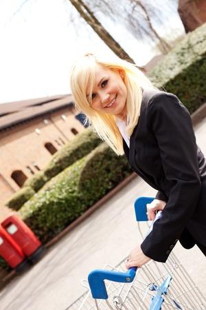 Angled view of a smiling attractive blonde woman pushing a shopping trolley across an empty carpark photo