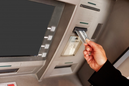 dispense: Cropped view of a female hand inserting a bank card into an ATM to begin a financial transaction