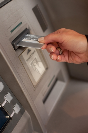 automatic transaction machine: Mano femenina que la inserción de una tarjeta bancaria en un cajero automático cajero automático para retirar o depositar dinero Foto de archivo