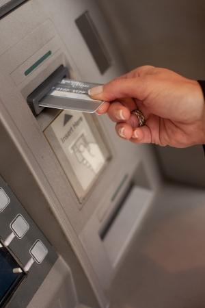 Vrouwelijke hand een bankpas bij een automatische bank teller machine te trekken of storten geld