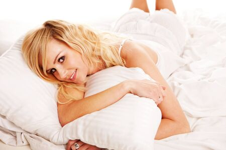 rejuvenated: Pretty blonde hugging her pillow as she awakes with a smile in the morning