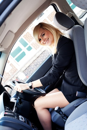 chauffeur: Beautiful businesswoman seated behind the steering wheel driving a ca in an urban environmentr