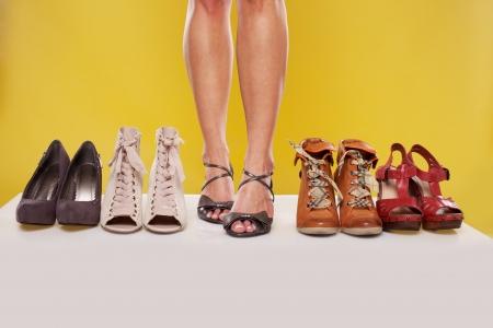 セクシーな女性脚線美サンダルを履いている靴ディスプレイ黄色のスタジオの背景の中心