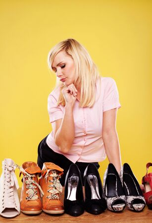 accessorize: Attractive blonde woman standing looking down at a row of different shoes trying to make a choice