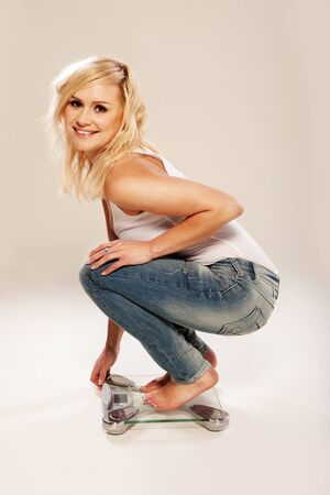 crouches: Slim and trim pretty blonde crouches low on a bathroom scale Stock Photo