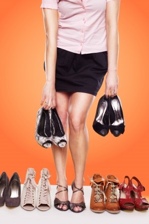 obsession: Cropped view of a woman with a passion for shoes and shapely legs wearing sandals standing in a line of shoes while also holding two pairs