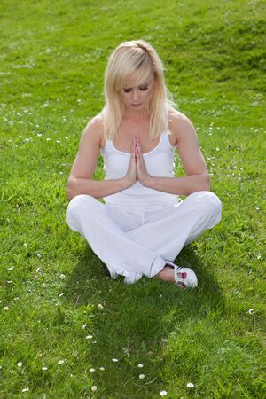 A pretty blonde girl sits on the green grass with her head bowed and hands clasped together in prayer seeking serenity through yoga