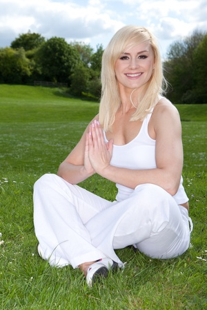 rejuvenated: Smiling beautiful young blonde woman sitting cross-legged on green grass with her hands clasped in a yoga pose