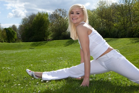 spliting: Young attractive blonde stretching outside on a field Stock Photo