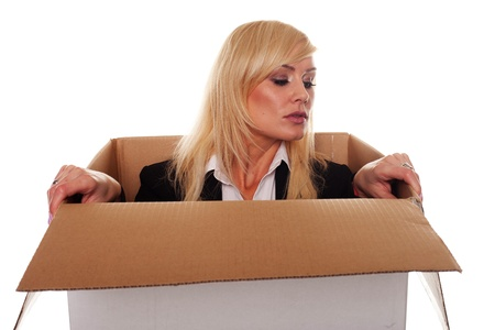 Scared young blonde emerging from a box isolated on white photo